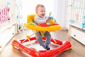 A happy baby in a baby walker