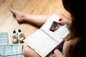 Woman placing baby's sonogram into baby's first-year memory book