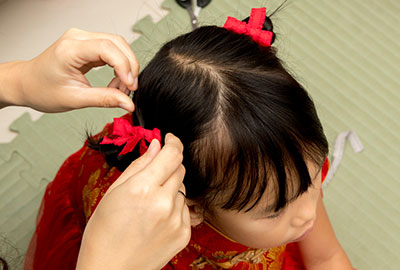 A mother using a baby ponytail holder for her daughter