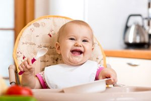 babysitting in high-chair with spoon and plate in a kitchen