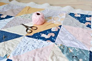 pink cotton thread, needle and scissors on the table