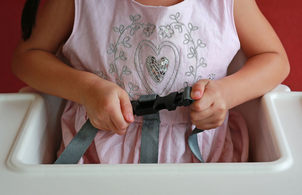 A child sitting on a best baby high Chair with fastening safety belt locked protection