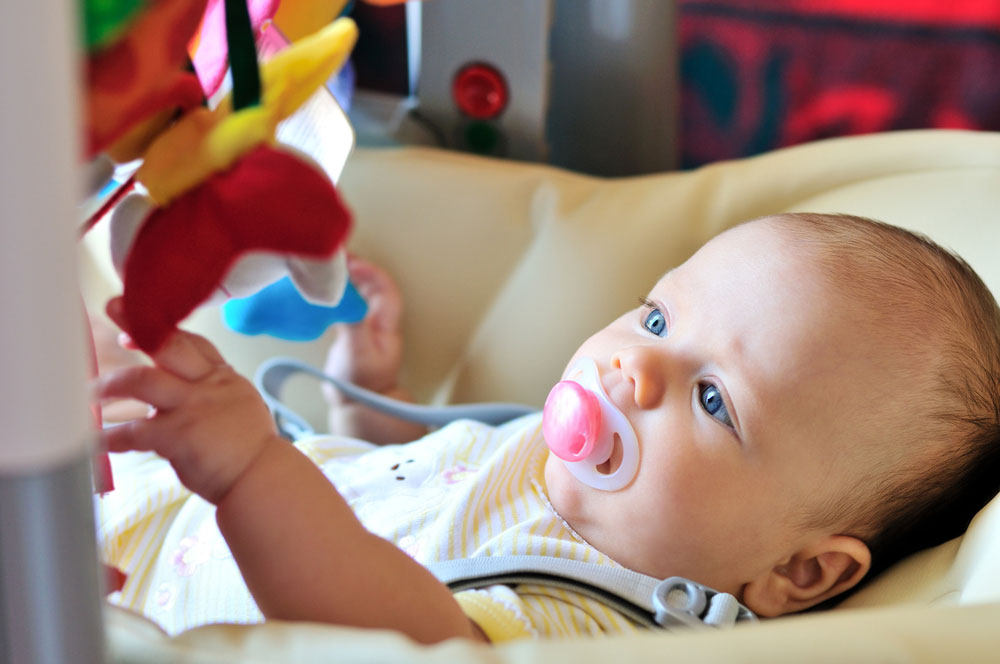 Best Baby Swing for Small Spaces--A baby playing with toys