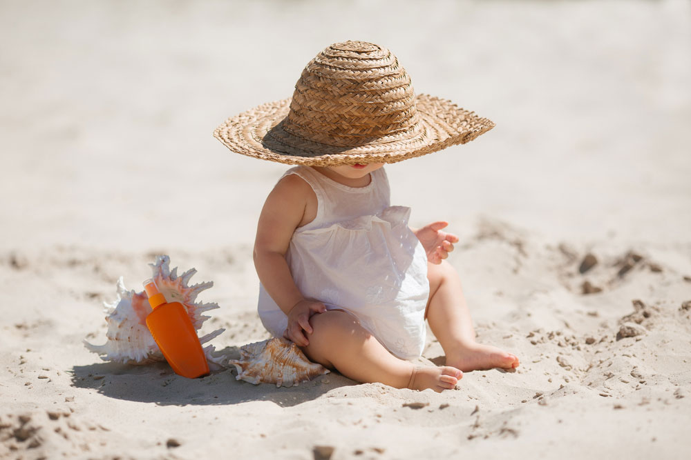 The baby is playing on the beach in the sun hat