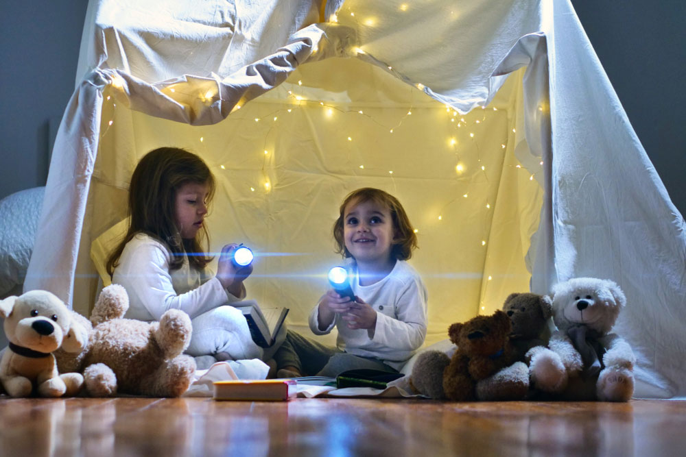 The children used a flashlight for indoor entertainment