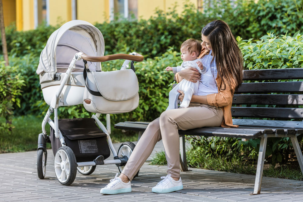 Mother and Baby Sitting next to Stroller