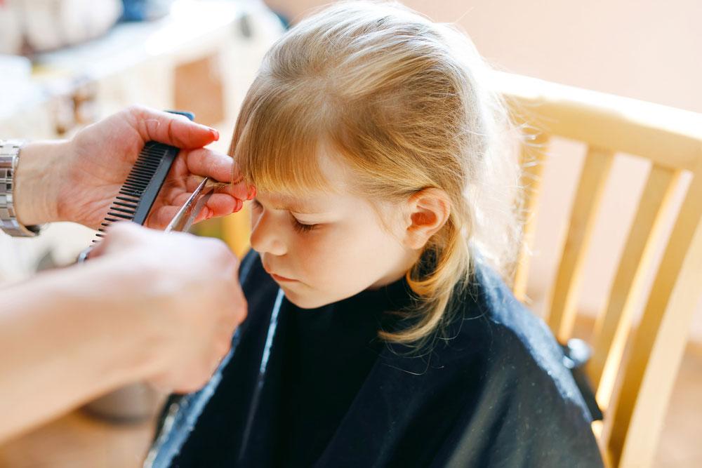 A little girl cutting her bangs