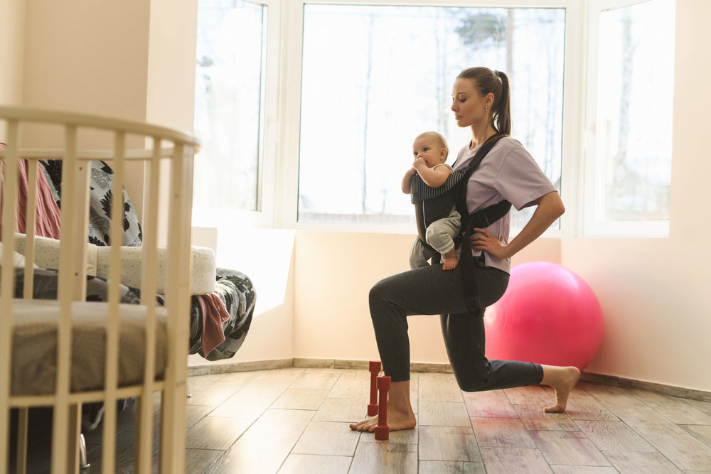 Woman working out while carrying a baby on a baby carrier